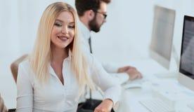 Работник женщины сидя на столе в офисе Стоковые Фото