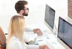 Работник женщины сидя на столе в офисе Стоковые Изображения RF