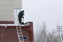 Работник извлекает снег и лед из крыши очищая крышу не исполняя с трудовыми правилами защиты стоковая фотография rf
