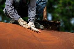 Работник извлекает краску бумагой песка стоковое изображение