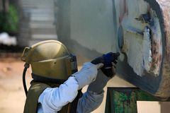 Работник извлекает краску взрывать песка воздушного давления стоковое фото rf