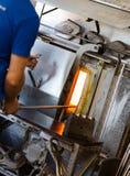 Работник изготовления нагревает стекло в печи для нагревать стекло Стоковая Фотография RF
