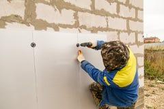 Работник изолирует дом от пластмассы пены Стоковые Фотографии RF