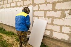 Работник изолирует дом от пластмассы пены Стоковые Изображения RF