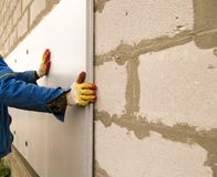 Работник изолирует дом от пластмассы пены Стоковая Фотография RF