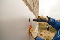 Работник изолирует дом от пластмассы пены Стоковые Изображения