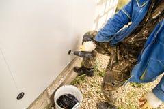 Работник изолирует дом от пластмассы пены Стоковое фото RF