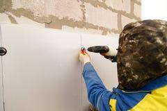 Работник изолирует дом от пластмассы пены Стоковая Фотография