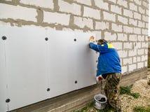 Работник изолирует дом от пластмассы пены Стоковое Изображение