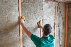 Работник изолирует загородный дом минеральных шерстей Стоковые Фото