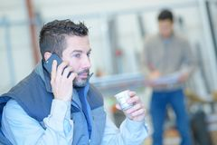 Работник имея переговор на телефоне во время breaktime стоковые изображения