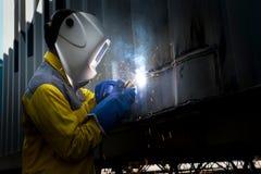 Работник индустрии с сталью заварки для того чтобы отремонтировать структуру контейнера Стоковые Изображения