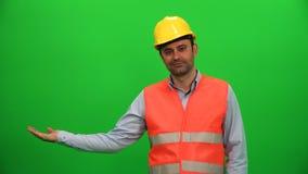 Работник инженера поднимая или представляя что-то на зеленом экране видеоматериал