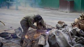 Работник использует газовый резак диссугаза кислорода для того чтобы отрезать большой объект металла в части на заводе по перераб акции видеоматериалы