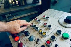 Работник использует пульт управления машины CNC для того чтобы обрабатывать материал стоковые фото