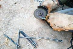 Работник использует угловую машину для того чтобы заточить болты, план конца-вверх стоковые фото