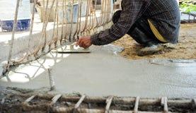 Работник используя деревянную лопатку для выравнивать конкретный пол стоковое изображение