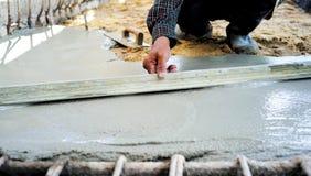 Работник используя деревянную лопатку для выравнивать конкретный пол стоковое изображение rf