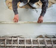 Работник используя деревянную лопатку для выравнивать конкретный пол стоковые фото