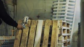Работник используя всасыватель для того чтобы покрасить деревянный паллет белый на мастерской акции видеоматериалы