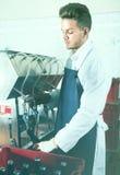 Работник используя машину для того чтобы разлить вино по бутылкам на фабрике игристого вина Стоковое Фото