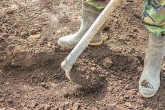 Работник используя раскопки сапки почва Стоковое фото RF