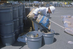 Работник лить содержание сумки в контейнер отходов на ненужном месте уборки на день земли на заводе Unocal Стоковое фото RF