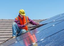 Работник и панели солнечных батарей стоковое фото