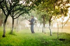 работник и фермер используя распыляя машину для пестицидов и инсектицида Стоковое Изображение