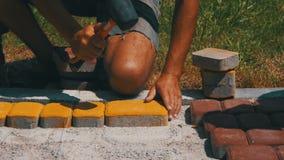 Работник кладет вымощая камни используя молоток видеоматериал
