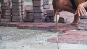 Работник кладет вымощая камни используя молоток сток-видео