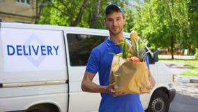 Работник компании по доставке держа продуктовую сумку, заказ еды, обслуживание супермаркета акции видеоматериалы
