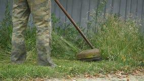 Работник косит травокосилку зеленой травы ручную на весенний день акции видеоматериалы