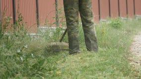 Работник косит травокосилку зеленой травы ручную на весенний день сток-видео
