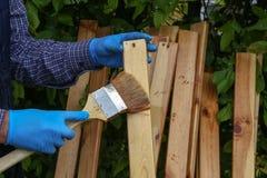 Работник красит деревянные предкрылки с защитной политурой стоковое фото rf