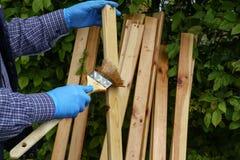 Работник красит деревянные предкрылки с защитной политурой стоковые фото