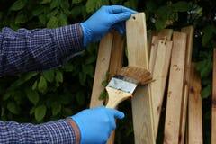 Работник красит деревянные предкрылки с защитной политурой стоковые изображения rf