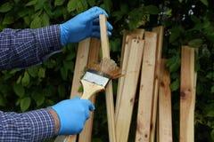 Работник красит деревянные предкрылки с защитной политурой стоковые фотографии rf