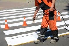 Работник красит пешеходный crosswalk Технические картина работника человека дороги и pedestr замечать Стоковое Фото