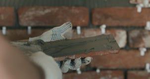 Работник крупного плана прикладывая конкретный клей к плитке кирпича Стоковое Фото
