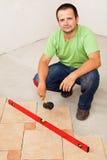Работник кладя керамические плитки пола стоковое изображение