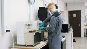 Работник лаборатории взгляда со стороны в форме кладет цилиндр в инструмент акции видеоматериалы