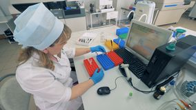 Работник лаборатории двигает пробы крови делая медицинские анализы в современной лаборатории видеоматериал