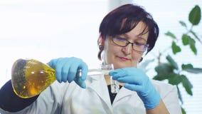 Работник льет химикаты от склянки в химической лаборатории акции видеоматериалы