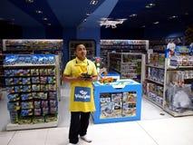 Работник магазина игрушек демонстрирует как лететь трутень игрушки Стоковое Фото