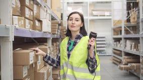 Работник магазина используя ярлыки блока развертки кода штриховой маркировки просматривая на коробках сток-видео