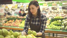 Работник магазина молодой женщины в коричневой рисберме на отделе с фруктами и овощами видеоматериал