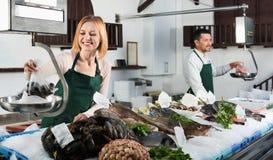 Работник магазина продавая свежих рыб и охлаженных морепродуктов Стоковые Фотографии RF