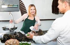 Работник магазина усмехаясь продающ свежих рыб и охлаженных морепродуктов Стоковые Фотографии RF