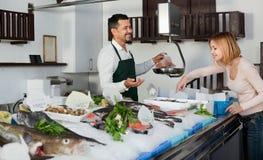 Работник магазина усмехаясь продающ свежих рыб и охлаженных морепродуктов Стоковые Изображения RF